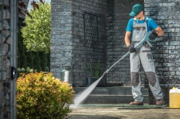 Driveway Pressure Washing. Caucasian Worker Cleaning Area in Front of the House.