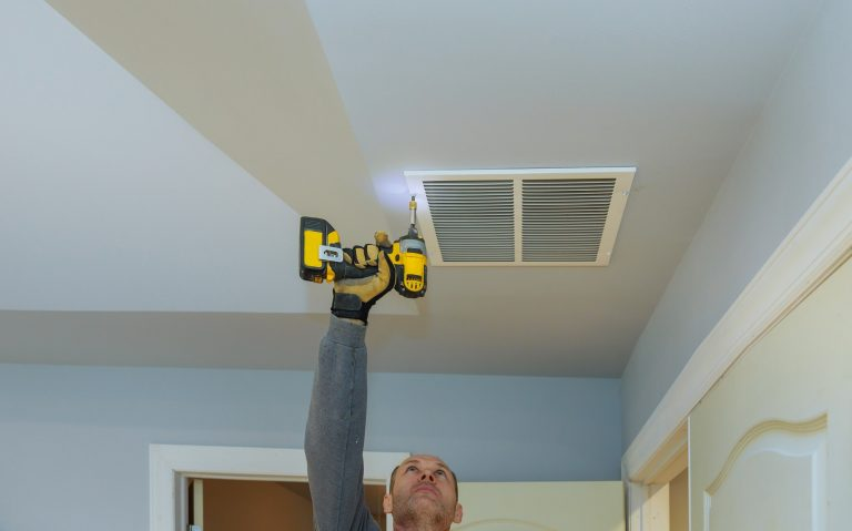 worker builder installing air conditioner ventilation cover construction of building