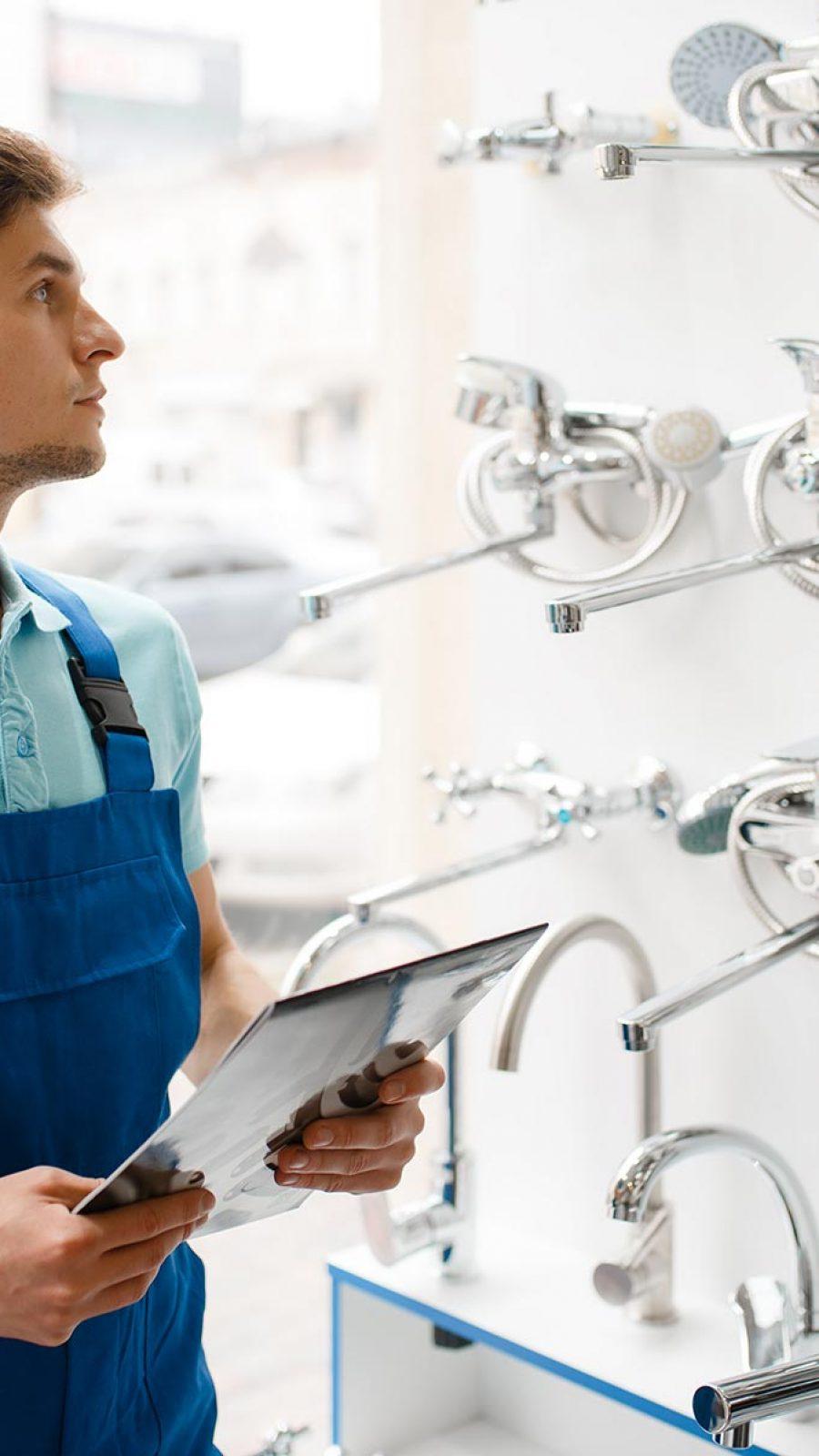 plumber-in-uniform-at-showcase-in-plumbering-store-PLGMWW8.jpg